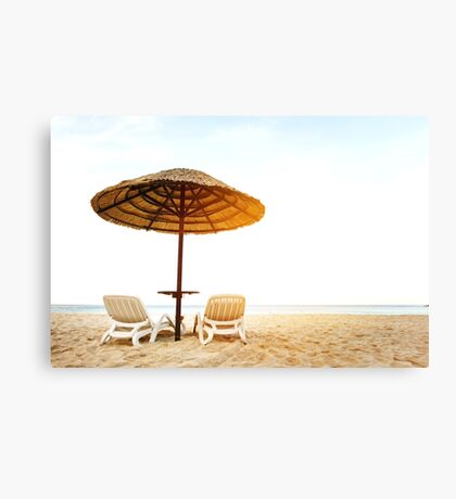 Sea resort with two chaise-longues under umbrella Canvas Print