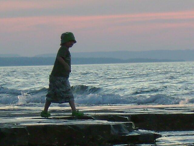 Kid skipping rock by Robert Lake