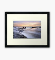 Waterfall flows across ocean rockshelf Framed Print