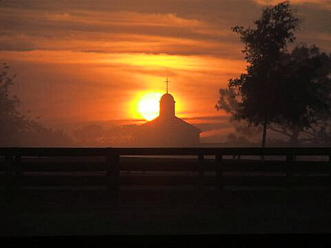 Sunrise behind Queen of Peace Church by Janice Makofski