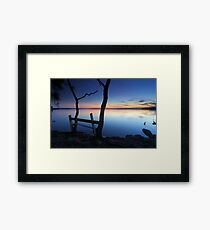 Rustic timber seat by the water on dusk sunset Framed Print