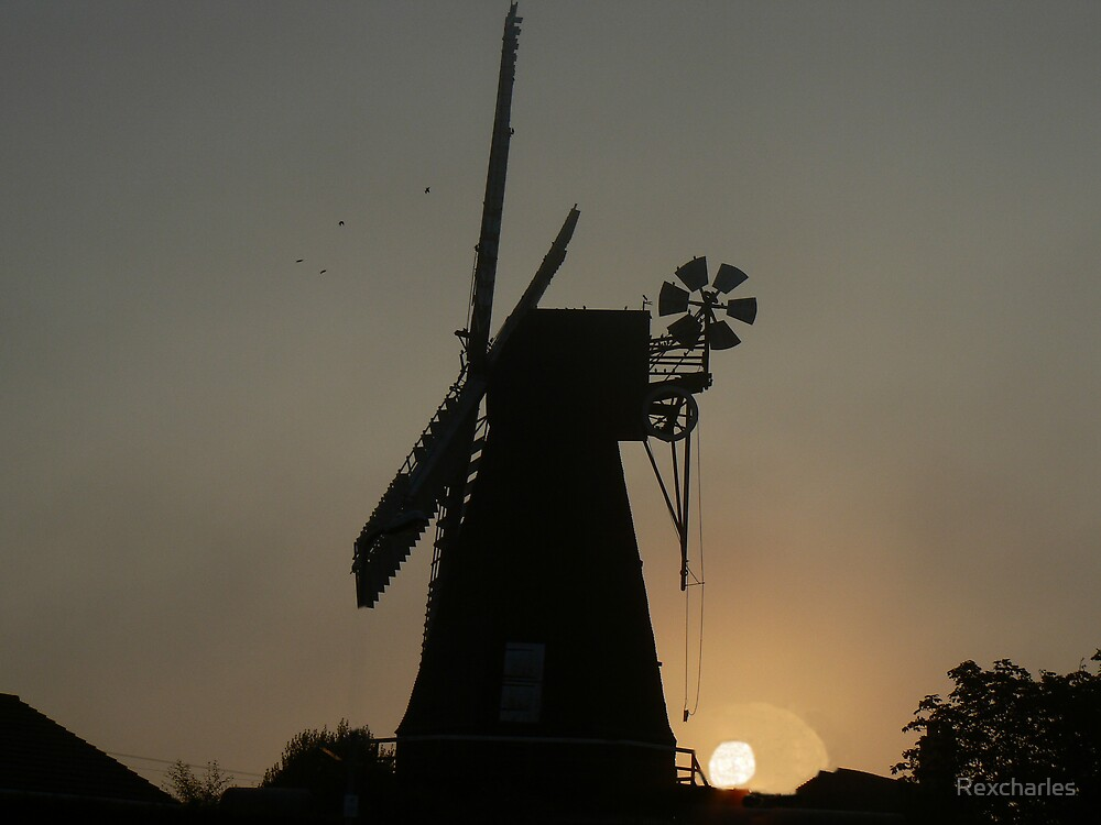 sunrise silhouetting  windmill by Rexcharles