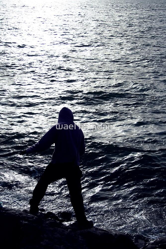 silhouette of man fishing at the sea by wael hamdan