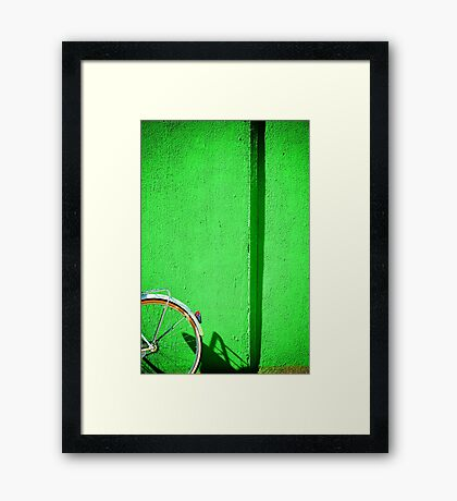 Bicycle wheel and green wall Framed Print