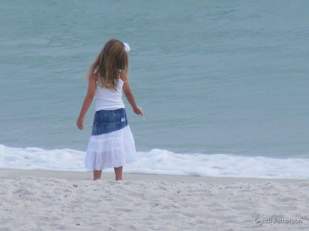 Little girl on the beach holding sand by Cyndi Jamerson