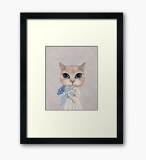 a cat with a blue flower Framed Print