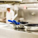 Commercial Pans with Chef in Background by dbvirago