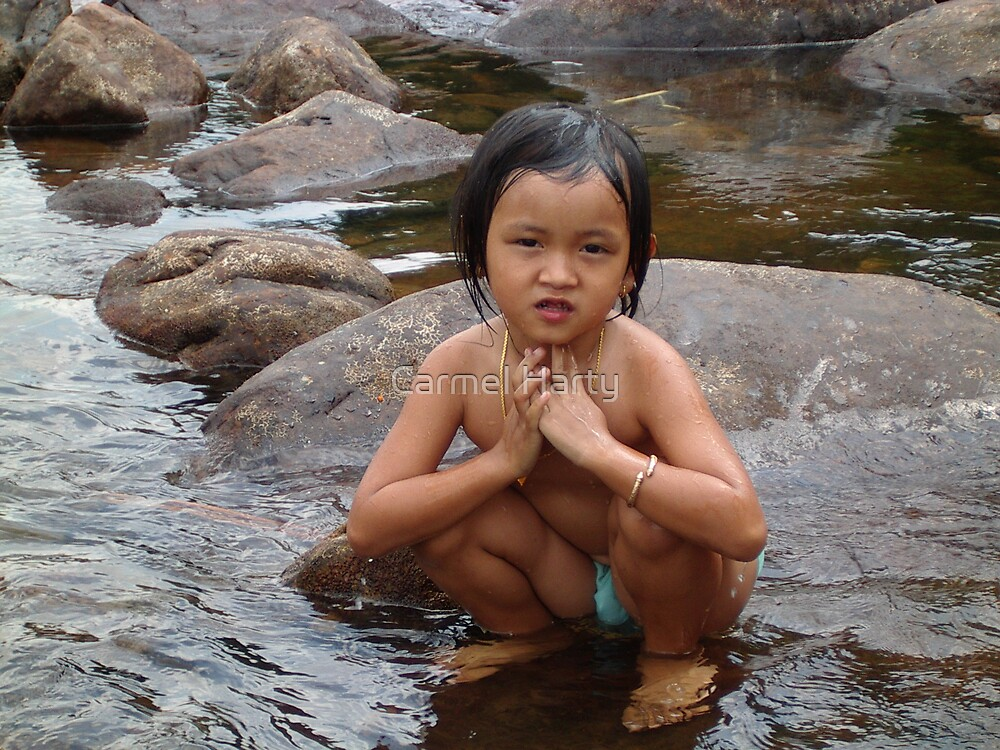 Cambodian girl on rocks  by Carmel Harty