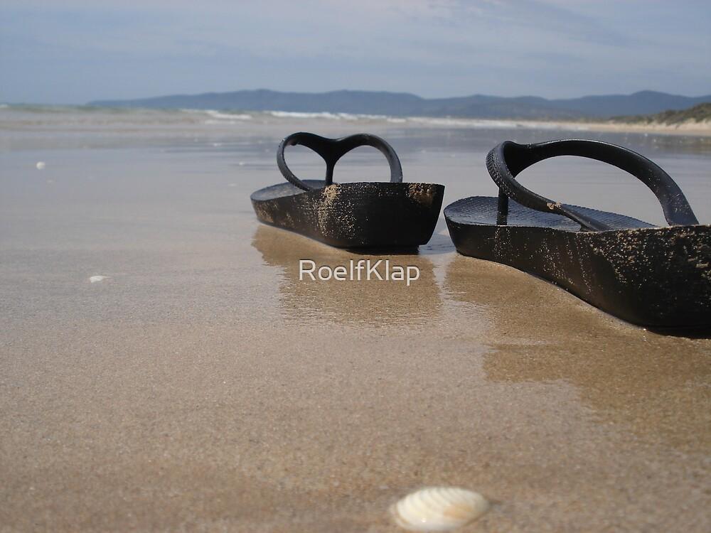 Thongs on beach by RoelfKlap