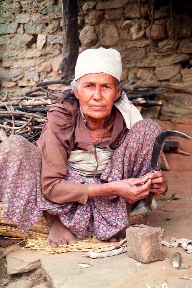 Woman cutting firewood in Nepal by jensNP