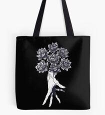 Hand with lotuses on black Tote Bag