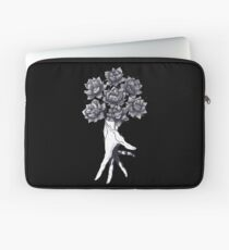 Hand with lotuses on black Laptoptasche