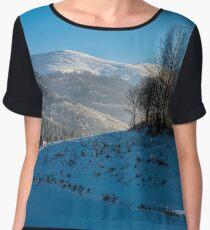 trees on snowy meadow in mountains Women's Chiffon Top