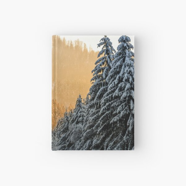 snowy road through spruce forest at sunset Hardcover Journal