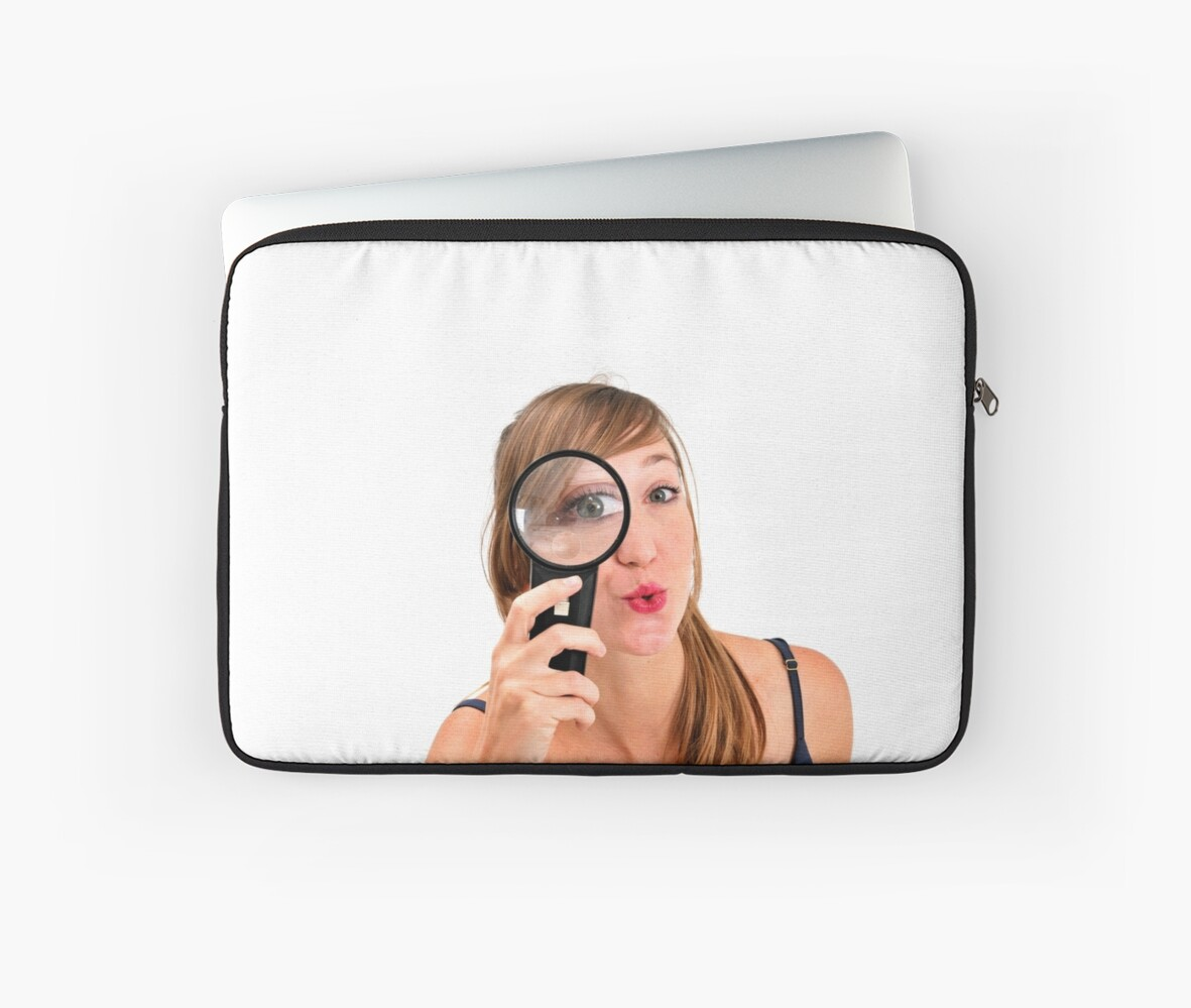 Young curious woman looks through a magnifying glass  by PhotoStock-Isra