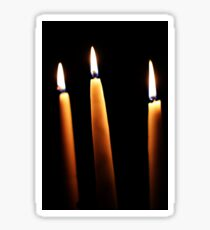 Three candles burning on a black background Sticker