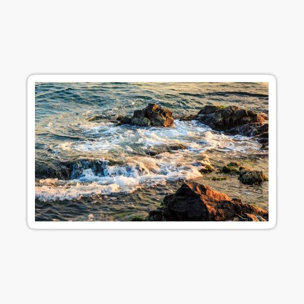 wave rolls onto the rocky coast Sticker