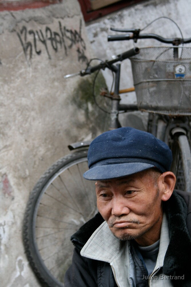 Chinese man sitting in an old Shanghai street by Julien Bertrand