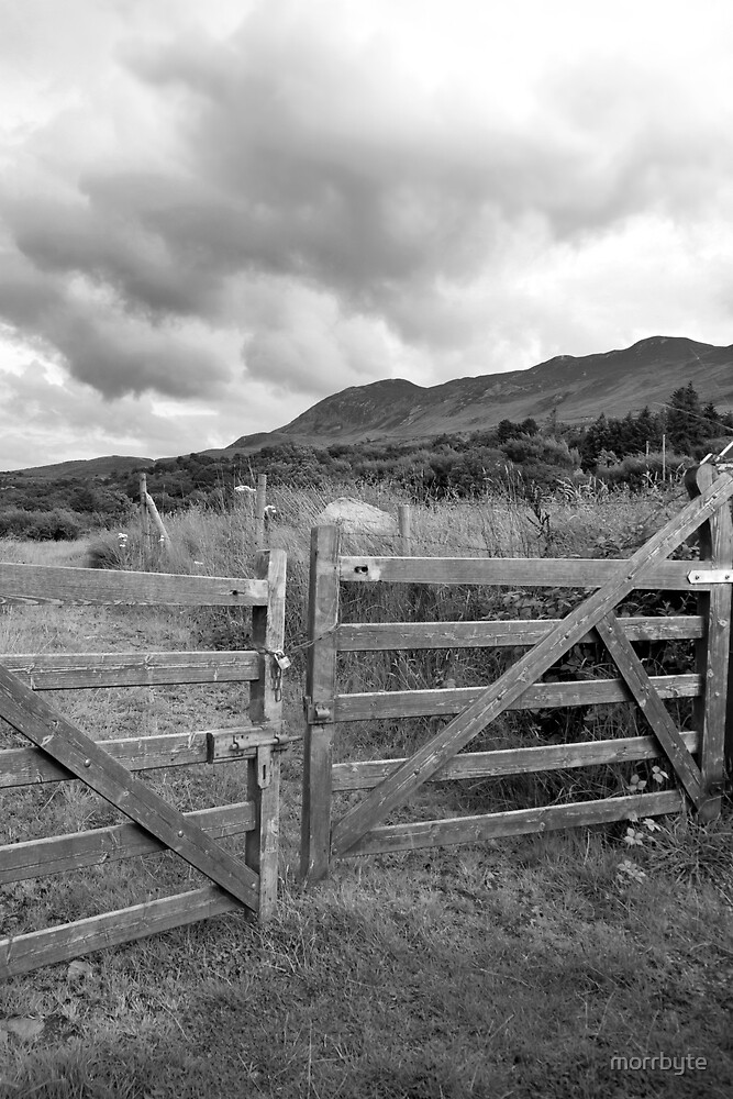 padlocked gate to mountains by morrbyte