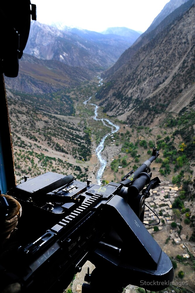 An aerial gunner surveys the surrounding area during a combat mission in Afghanistan. by StocktrekImages