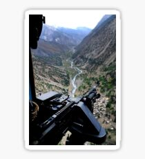 An aerial gunner surveys the surrounding area during a combat mission in Afghanistan. Sticker