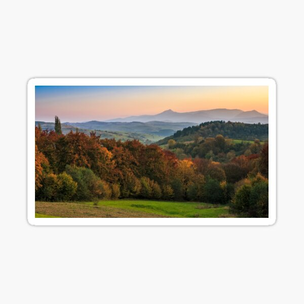 sunset over autumn forest in hazy mountains Sticker
