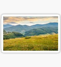 grassy meadow in mountains at sunrise Sticker