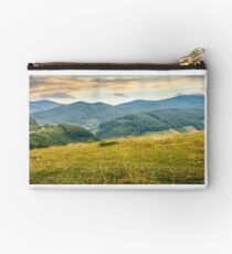 grassy meadow in mountains at sunrise Studio Pouch