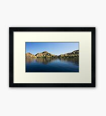 Coastline of mountains reflected  in blue ocean. Framed Print