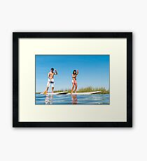 Man and woman stand up paddleboarding Framed Print
