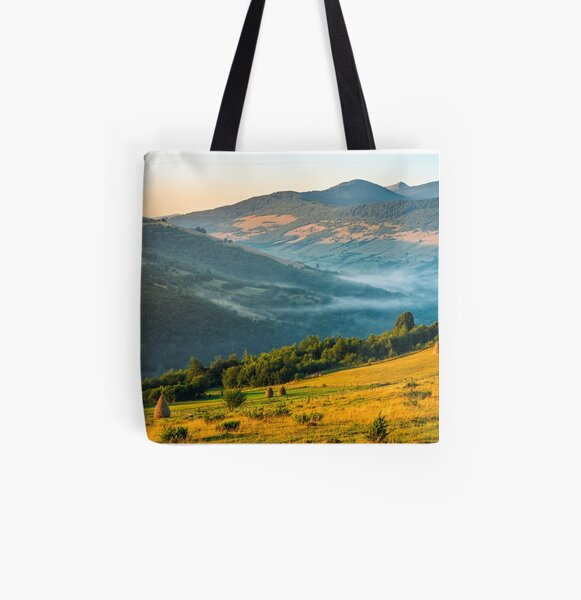 stacks of hay on the hill side All Over Print Tote Bag