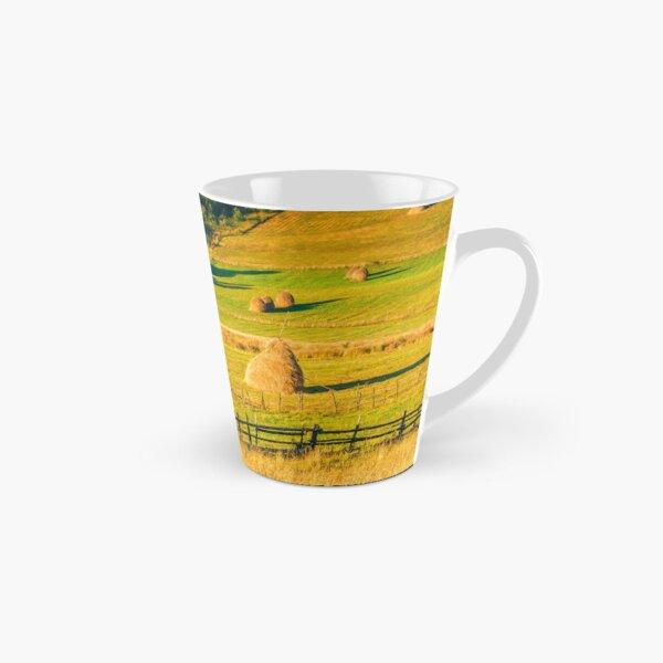 haystacks and a trees on a hillside meadow Tall Mug