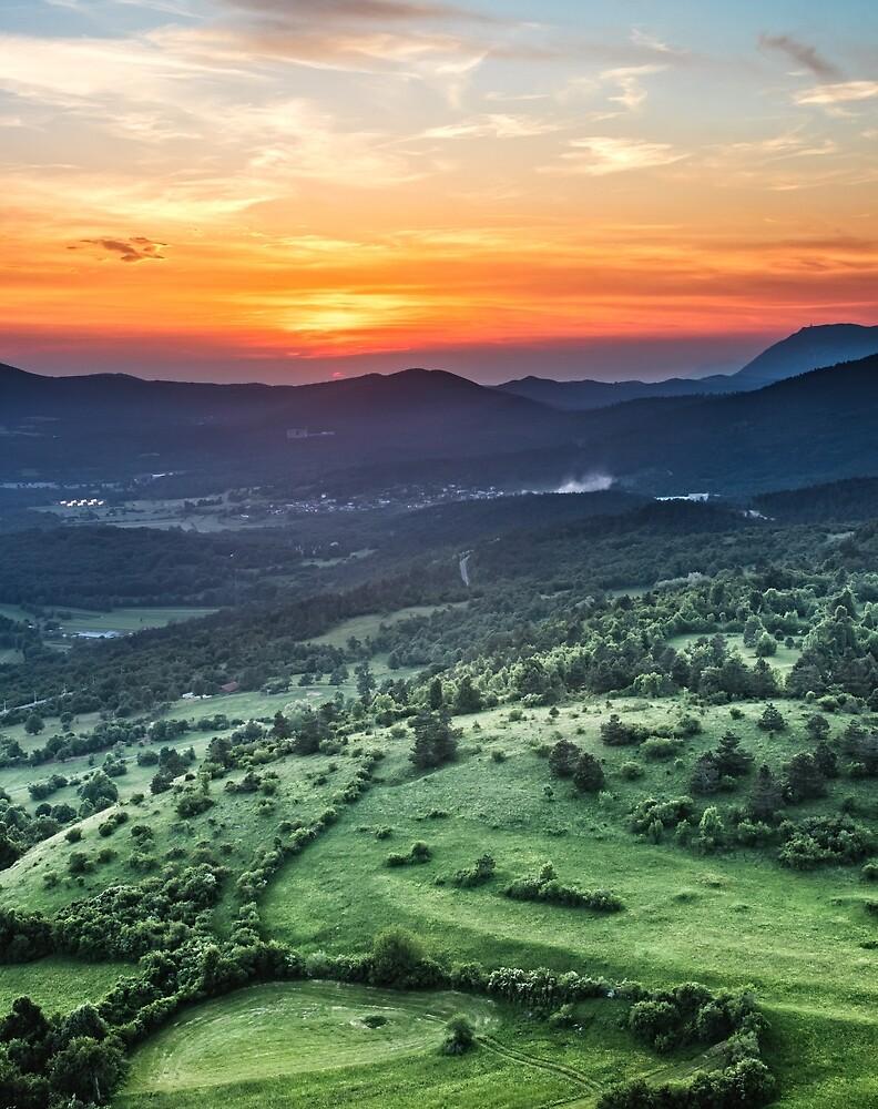 Beautiful sunset behind green fields by Patrik Lovrin