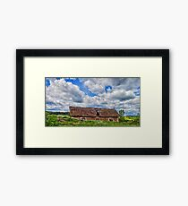 Blue cloudy sky over stork sitting on the edge of barn, Poland, Europe  Framed Print
