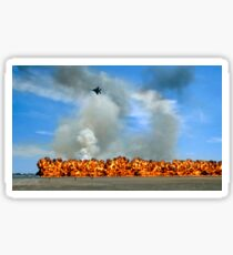 Pyrotechnics explode while an F-15 flies over to simulate an air-to-ground attack. Sticker