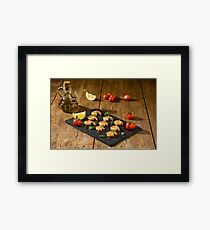 Shrimp skewers with tomatoes, lemon and oil on a stone Framed Print
