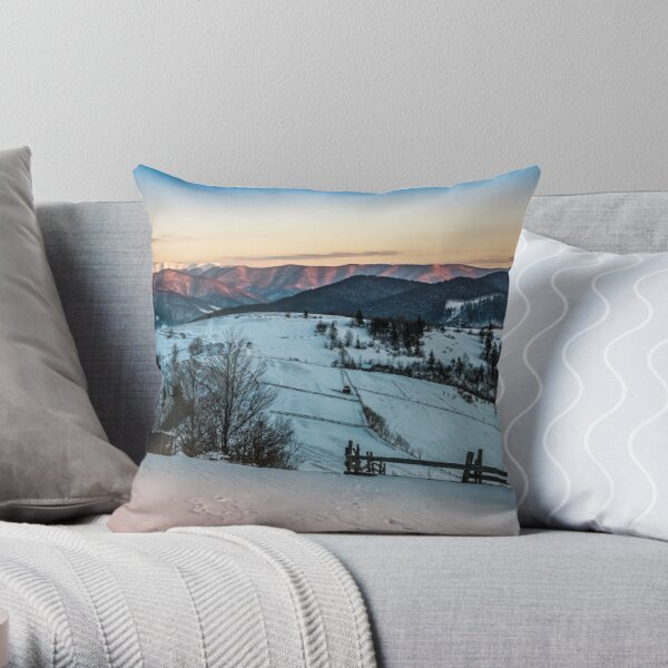 fence on snowy mountain slope near the forest in winter Throw Pillow