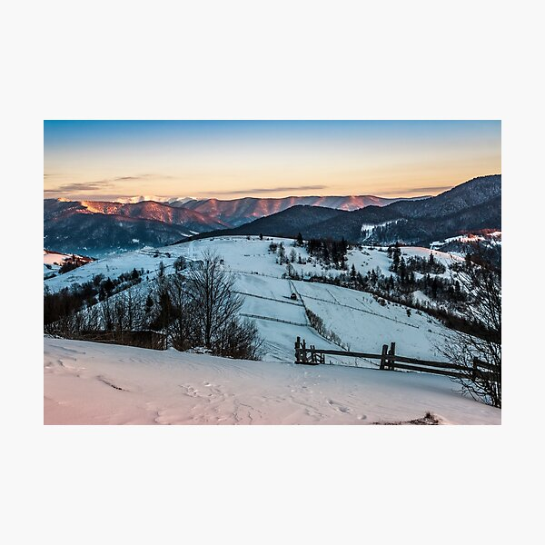 fence on snowy mountain slope near the forest in winter Photographic Print
