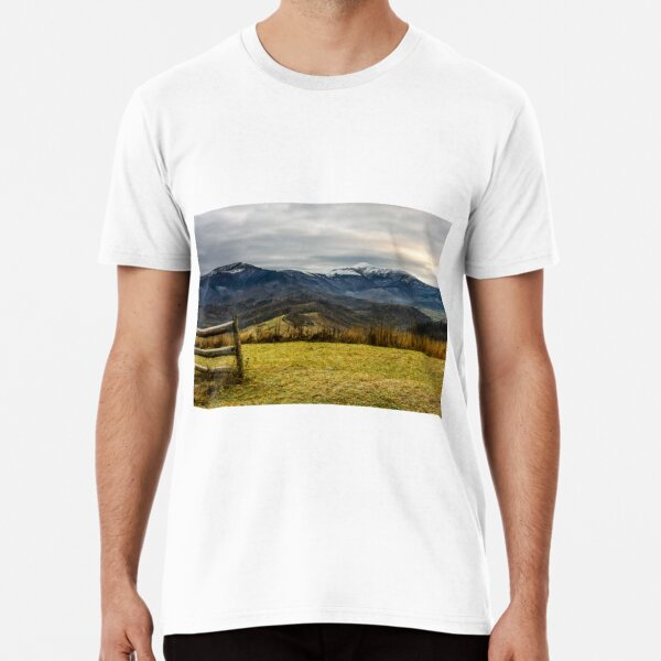 fence on the meadow in snowy mountains Premium T-Shirt