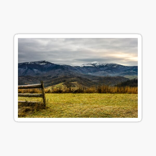 fence on the meadow in snowy mountains Sticker