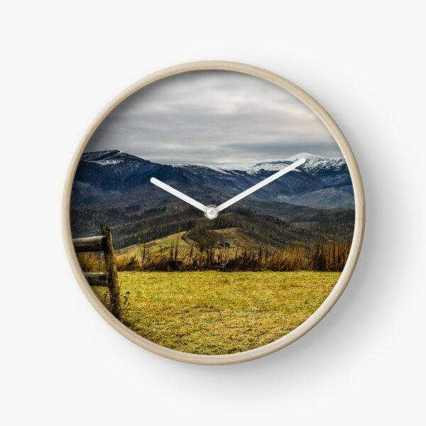 fence on the meadow in snowy mountains Clock