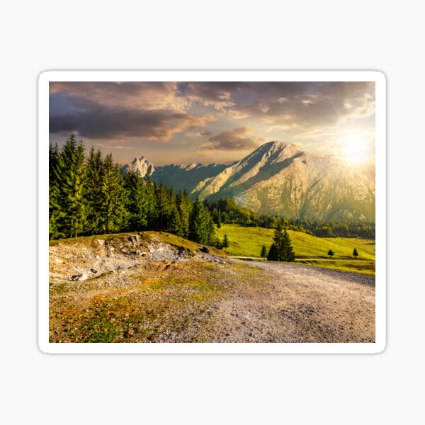 road through forest to high mountains at sunset Sticker