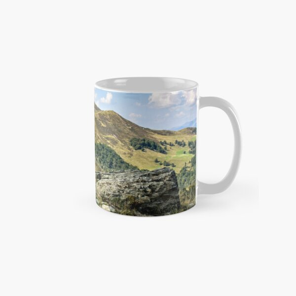 mountain landscape with stones in the grass on hillside and blue sky Classic Mug