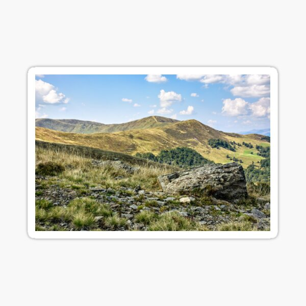 mountain landscape with stones in the grass on hillside and blue sky Sticker
