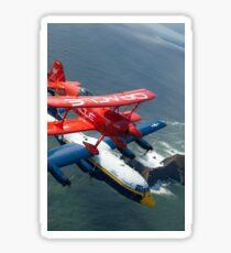 A C-130 Hercules Fat Albert aircraft and biplane fly over San Francisco Bay. Sticker