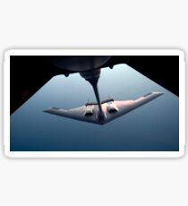 A B-2 Spirit bomber conducts a refueling with a KC-10 Extender. Sticker