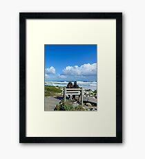 Women watching the seashore Framed Print