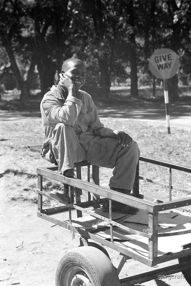ZIMBABWEAN man sitting on a squash cart by garycraft
