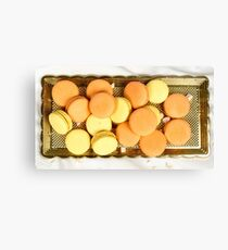 Stack of orange and yellow macaroon biscuits isolated on white. Canvas Print