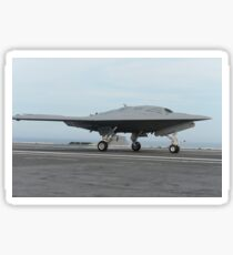 An X-47B unmanned combat air system conducts a touch and go landing. Sticker